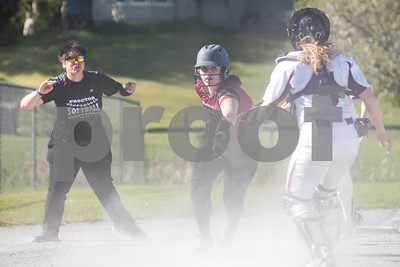 Proctor's Rachel Stuhlmueller races towards home but is caught from behind my Black River's Morgan Brown from behind during a run down. Coach Abby Bennett is pictured on the left, giving direction. (Robert Layman / Staff Photo)