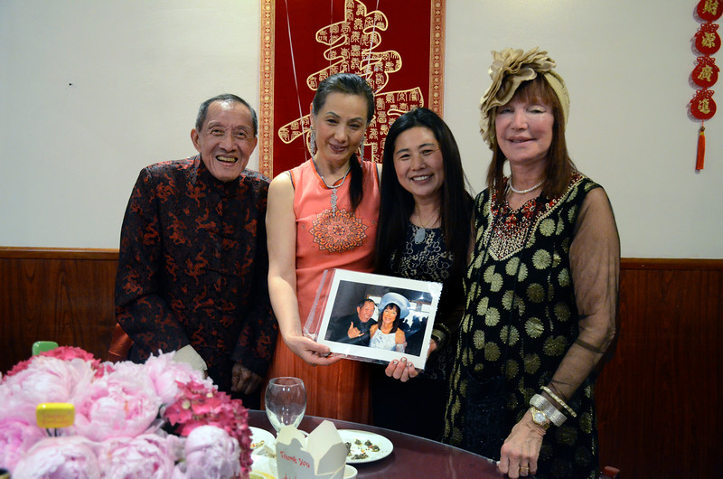 "Henry Him, left, with a fabricated TIME Magazine ""man of the year"" type cover at his 80th birthday party at Dong Bei Mama Restaurant. Restaurant owner 2nd on left. Sheila Ash on right."