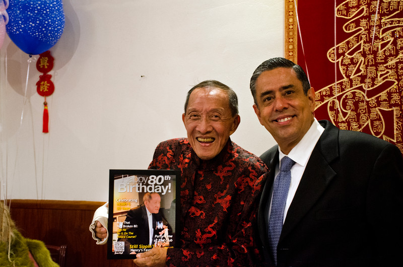"""Henry Him, left, with a fabricated TIME Magazine """"man of the year"""" type cover at his 80th birthday party at Dong Bei Mama Restaurant"""