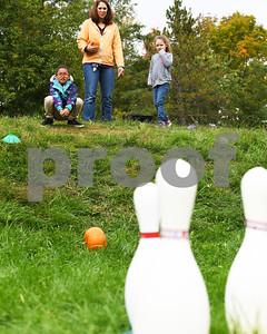 Marianna White, left, smiles as her pumpkin rolls towards a set of pins during the Northeast Elementary's annual Fall Festival Thursday morning.