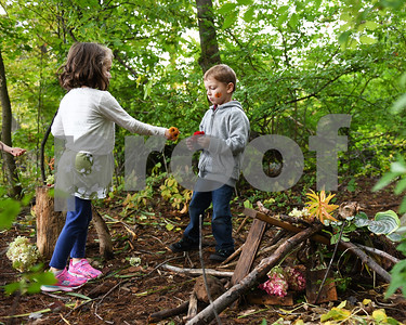 Savannah Massey, left, hands a flower to George Ferguson as the pair work to construct fairy houses behind Northeast Elementary School during the annual Fall Festival at Northeast Elementary School Thursday morning.