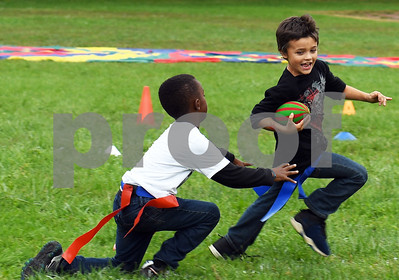Aaron Jones, right, barley evades an attempted flag removal by Elijah Gillespeduring the annual Fall Festival at Northeast Elementary School Thursday morning.