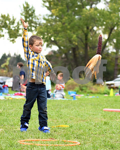 Connor Smart-Walsh, kindergartener at Northeast Elementary, chucks an ear of corn into a basket during the annual Fall Festival at Northeast Elementary School Thursday morning.