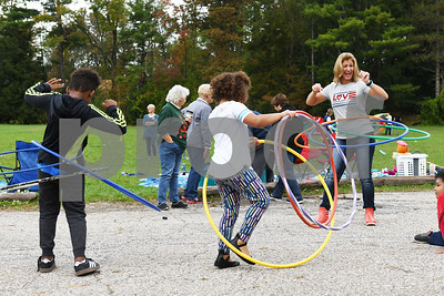 First grade teacher Leah Abatiell, right, smiles as her classmates try to follow her lead while hula-hooping during the Northeast Elementary's annual Fall Festival Thursday morning.