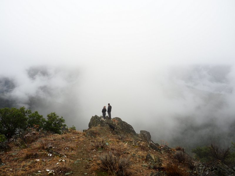 Two people standing overlooking a foggy valley