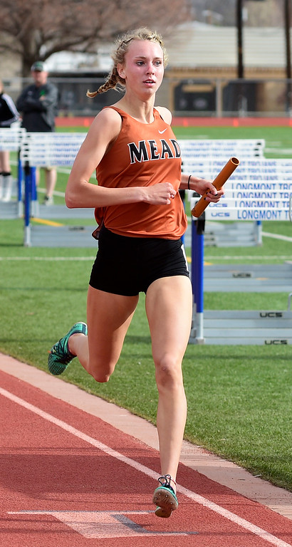 . LONGMONT, CO - April 20, 2019: Abby Glenn, of Mead, finishes a relay at the Boulder County Track and Field Championships in Longmont. (Photo by Cliff Grassmick/Staff Photographer)