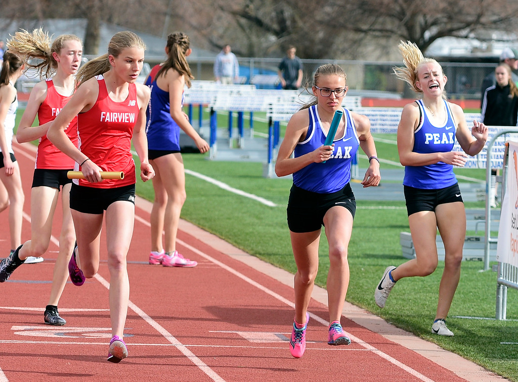 . LONGMONT, CO - April 20, 2019:  Jenna Howard, right, of Peak to Peak, in the 4X800 relay at the Boulder County Track and Field Championships in Longmont. (Photo by Cliff Grassmick/Staff Photographer)