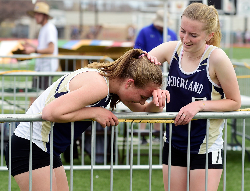 . LONGMONT, CO - April 20, 2019:  Megan Feeley, right, of Nederland, comforts her teammate, Helen Cross, after the 1600 meters  at the Boulder County Track and Field Championships in Longmont. (Photo by Cliff Grassmick/Staff Photographer)
