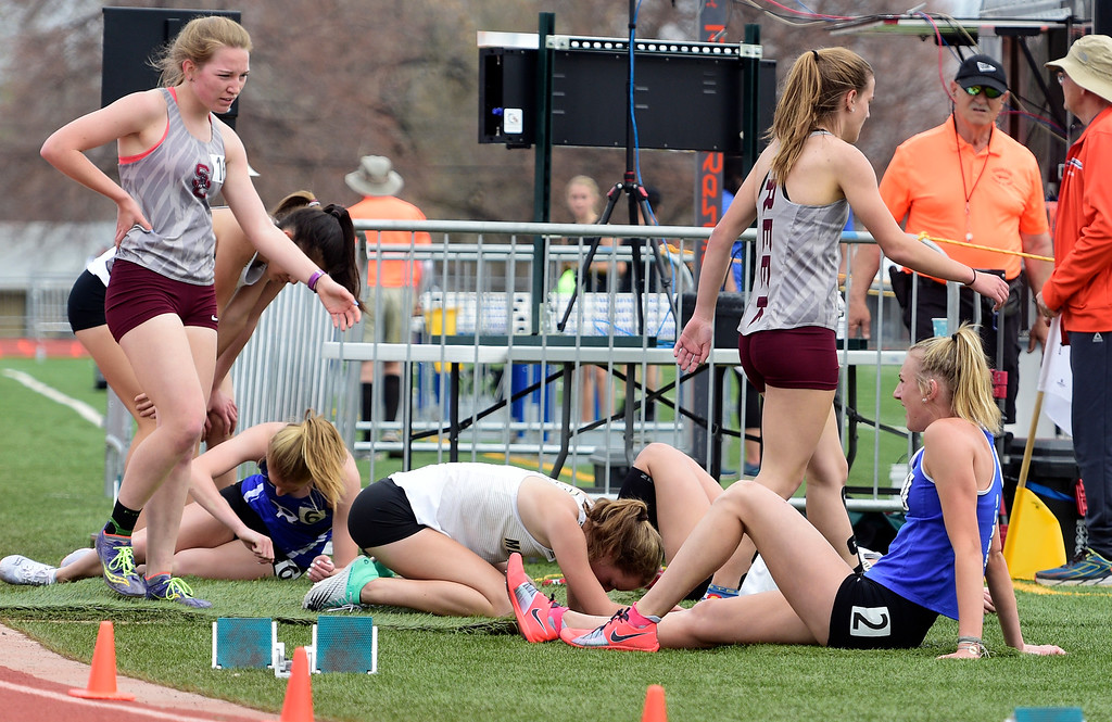 . LONGMONT, CO - April 20, 2019: Runners collapse after running the 1600 meters at the Boulder County Track and Field Championships in Longmont. (Photo by Cliff Grassmick/Staff Photographer)