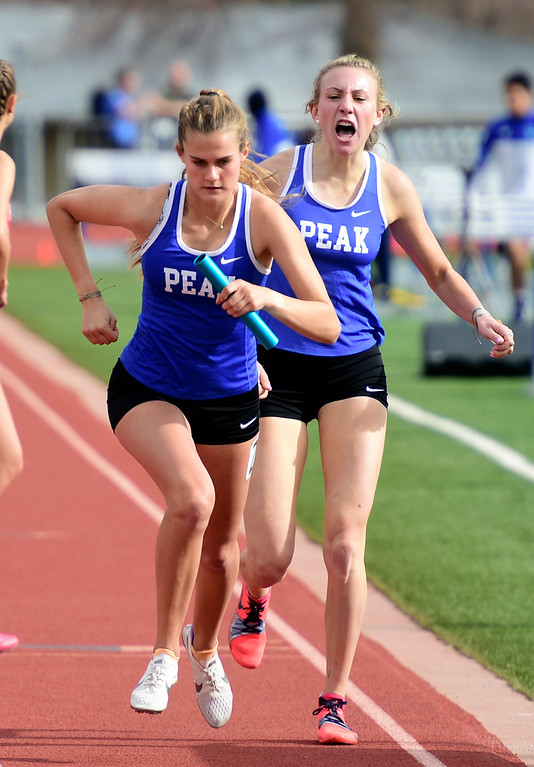 . LONGMONT, CO - April 20, 2019:  Tiana Bradfield, of Peak to Peak, takes the bouton from Quinn McConnell in the 4X800 meter relay at the Boulder County Track and Field Championships in Longmont. (Photo by Cliff Grassmick/Staff Photographer)