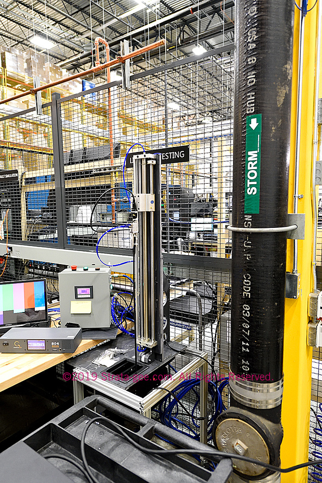 Crestron testing jig conducting a lifecycle test on a cable retractor for a conference table