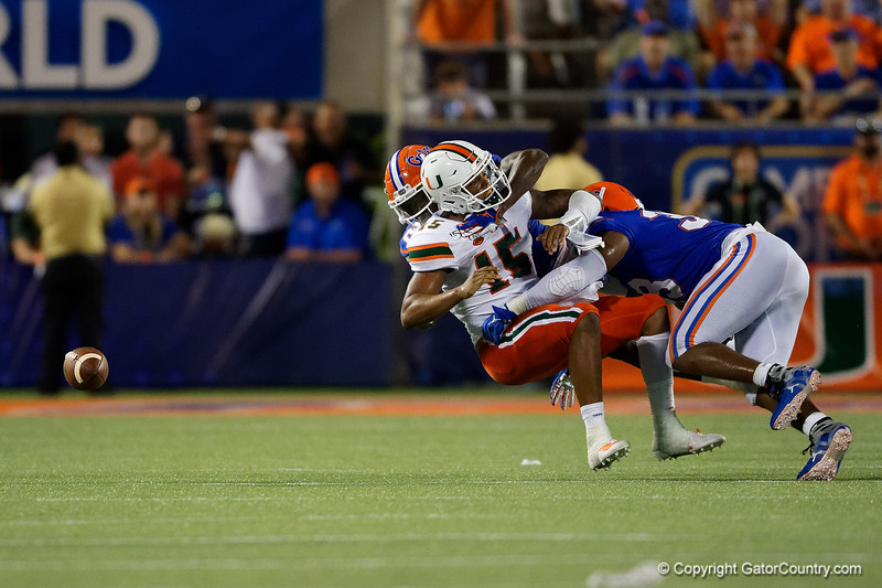 Florida Gators linebacker David Reese II (33) and Florida Gators defensive back Trey Dean III (21) combine for a tackle on Miami Hurricanes quarterback Jarren Williams (15)  as the University of Florida Gators hold on to win 24-20 over the University of Miami Hurricanes at Camping World Stadium in Orlando, Florida.  August 23rd, 2019. Gator Country Photo by David Bowie.