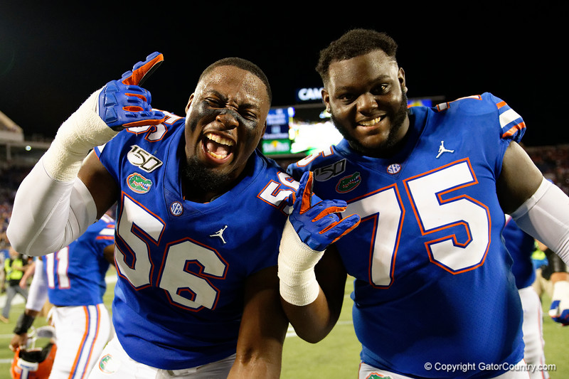 Florida Gators offensive lineman Jean Delance (56) and Florida Gators offensive lineman T.J. Moore (75) as the University of Florida Gators celebrate after holding on to win 24-20 over the University of Miami Hurricanes at Camping World Stadium in Orlando, Florida.  August 23rd, 2019. Gator Country Photo by David Bowie.