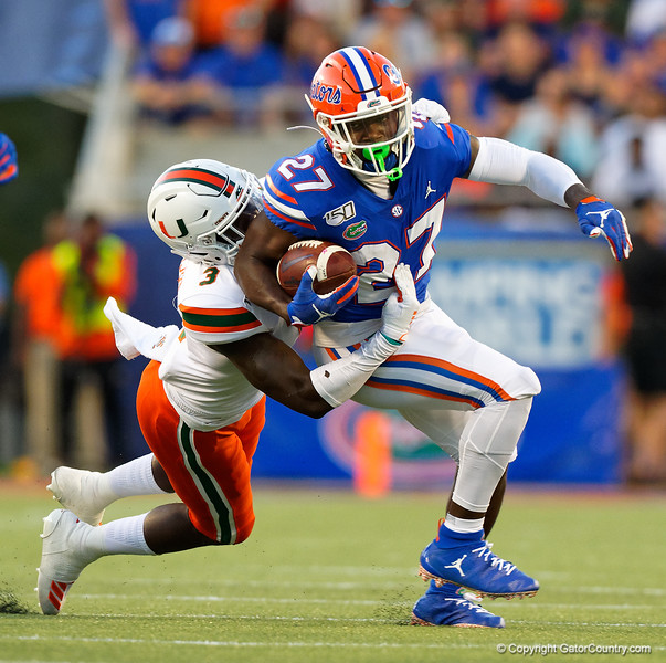 Florida Gators running back Dameon Pierce (27) rushes as Miami Hurricanes linebacker Gilbert Frierson (3) makes the tackle as the University of Florida Gators hold on to win 24-20 over the University of Miami Hurricanes at Camping World Stadium in Orlando, Florida.  August 23rd, 2019. Gator Country Photo by David Bowie.