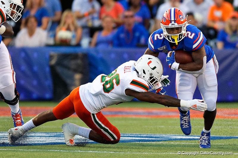 Florida Gators running back Lamical Perine (2) rushes upfield as Miami Hurricanes defensive back Gurvan Hall Jr. (26) makes the tackle as the University of Florida Gators hold on to win 24-20 over the University of Miami Hurricanes at Camping World Stadium in Orlando, Florida.  August 23rd, 2019. Gator Country Photo by David Bowie.