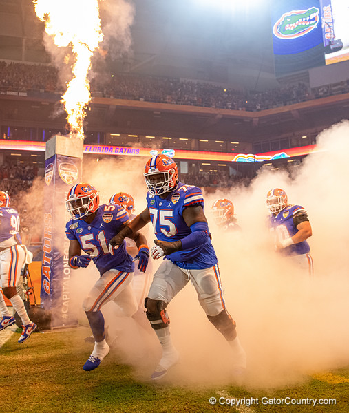 Florida Gators offensive lineman T.J. Moore (75) and Florida Gators linebacker Ventrell Miller (51) as the Florida Gators run onto the field prior to kickoff in the 2019 Capital One Orange Bowl in Miami Gardens, Florida.  December 30th, 2019. Gator Country Photo by David Bowie.