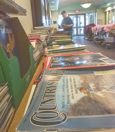 "James Neiss/staff photographer <br /> Lockport, NY - Lou Hoke of Lockport peruses the magazines at The Friends of the Lockport Public Library ""Spectacular Spring"" Used Book Sale."