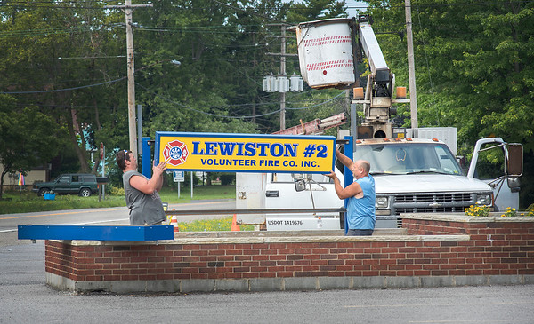 James Neiss/Staff Photographer<br /> Niagara Falls, NY - Sign makers James Stephanski and Doug Adams with Ad-A-Sign in Wheatfield, size up a new sign for installation at Lewiston #2 Volunteer Fire Co. Inc. on Saunders Settlement Road.