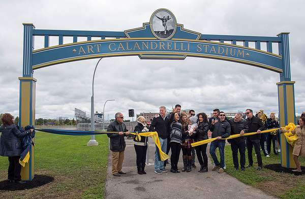 James Neiss/staff photographer <br /> Niagara Falls, NY - Calandrelli family and friends cut the ribbon officially naming the Niagara Falls High School stadium Art Calandrelli Stadium. Ellen Latham, founder of Orange theory Fitness and Niagara Falls High School graduate, purchased the naming rights to honor her father, a former coach there.