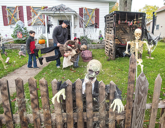 James Neiss/staff photographer <br /> Lockport, NY - Nick Corraine, center, helps his kids Noah, 10, and Ezra, 4, move a body to the yard of their South Street home. The boys mother was nowhere to be seen or heard from.
