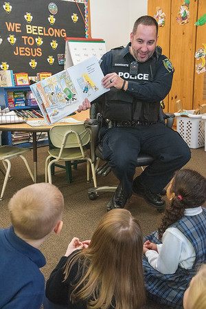 """James Neiss/staff photographer <br /> Lockport, NY - Lockport Police Officer Luke Giansante reads the book """"Police Officers on Patrol,"""" by Kersten Hamilton and R.W. Alley, to first graders on Monday at DeSales Catholic School as part of Lockport Blue."""
