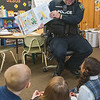 "James Neiss/staff photographer <br /> Lockport, NY - Lockport Police Officer Luke Giansante reads the book ""Police Officers on Patrol,"" by Kersten Hamilton and R.W. Alley, to first graders on Monday at DeSales Catholic School as part of Lockport Blue."