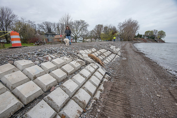 James Neiss/staff photographer <br /> Olcott, NY - Dorothy O'Sullivan walks her dog Sully on a newly constructed retaining wall behind her McKee Street waterfront home. Sully said the retaining wall is a lot wider now.