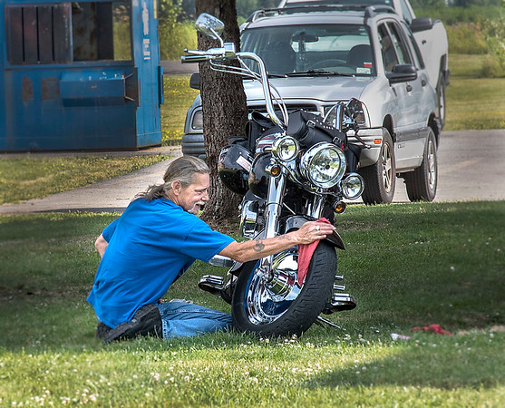 James Neiss/Staff Photographer<br /> Lockport, NY - Wayne Johnson found some shade to give a spit polish shine to his 2001 Harly Davidson Fat Boy motorcycle outside his Dysinger Road apartment.