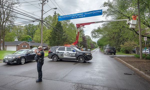 James Neiss/staff photographer <br /> Lockport, NY - Lockport Lt. Kendra Ditullio helps to keep workers safe as they hoist a banner over East Avenue at the corner of Davison Road for the annual 100 American Craftsmen art show at the Kenan Center on May 31 - June 2.