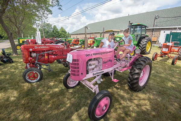 James Neiss/Staff Photographer<br /> Lockport, NY - Grandpa Gil Eaton of Lockport, explains how a tractor works to his granddaughter Adysen Chase, 7, also of Lockport, during their visit to the farm machinery on display at the Niagara County Fair.