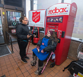 James Neiss/staff photographer  Town of Niagara, NY - Latoya Scott of Niagara Falls drops a few dollars in the Salvation Army kettle supervised by bell ringer Brenda Brown, at the Tops Market on Military Road. Brown has been a bell ringer for over 18 years.