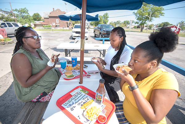 James Neiss/Staff Photographer<br /> Niagara Falls, NY - Denita Works, Kadeshia Saffold and Tasheena Brundidge enjoy 99 cent hot dogs on Customer Appreciation Day at Porky's Hotdogs on Hyde Park Boulevard.