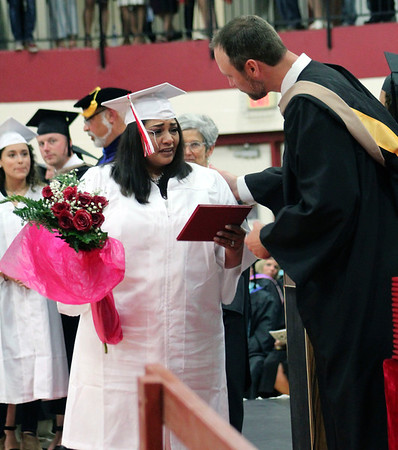 Roger Schneider | The Goshen News<br /> The mother of Annalissa Calderon, Pauline Uribe, accept's a diploma from Assistant Superintendent Alan Metcalfe on behalf of her daughter Sunday during the Goshen High School graduation ceremony. Calderon was killed in a car crash in February.