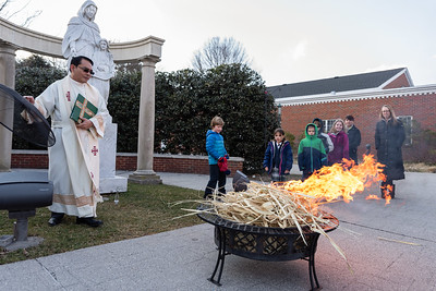 Fr. Ramel O. Portula burns palms from last year's Palm Sunday with parishioners in attendance outside of St. Ann Church in Arlington March 4, 2019.