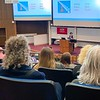 """Photo of Elisa Kosarin, conference keynote speaker, delivers her presentation, """"Achieving Buy-in for Your Volunteer Program,"""" inside a lecture hall in the Donald P. Corbett Business Hall on the campus of the University of Maine in Orono."""