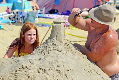 Melania Perry (left) watches her dad Micheal work on their sand sculpture during the 33rd annual New Jersey Sandcastle Contest was held at the 18th Ave beach in Belmar on Wednesday July 17, 2019. (MARK R. SULLiVAN/ THE COAST STAR)