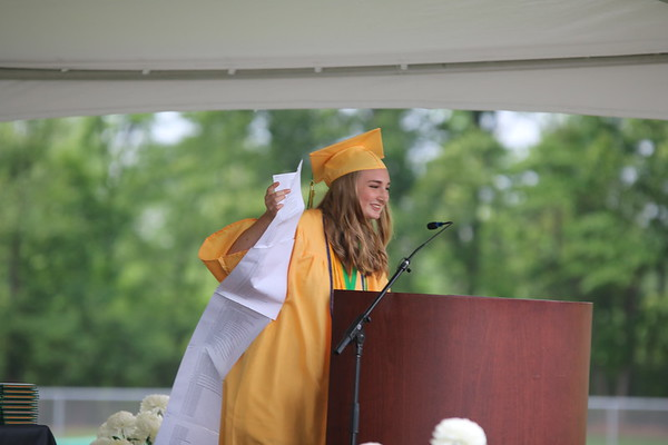 AIMEE AMBROSE | THE GOSHEN NEWS <br /> Kailee Miller holds a list of Northridge High School student accomplishments — pages stretching from her head to the stage floor — as she delivers the student address during the school's graduation ceremony in Middlebury Sunday.