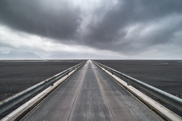 Looking across the long Skeidararsandur bridge with a storm on the horizon in Iceland
