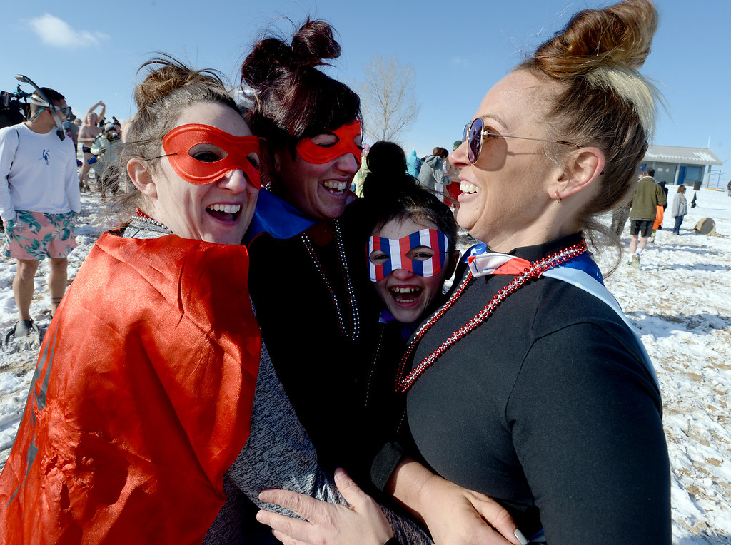 . BOULDER, CO - January 1, 2019: Shiloh May, left, Maddy Broadrick,  Kenzy Broadrick, 10, and Sara Lister,  huddle up to et warm during  the annual Polar Plunge at the Boulder Reservoir on January 1, 2019. For a video and photos, go to dailycamera.com.  (Photo by Cliff Grassmick/Staff Photographer)