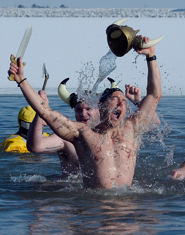 . BOULDER, CO - January 1, 2019:  Garrett Jimenez,  front, and Dave Marucheau,  and their Viking team have conquered the water during  the annual Polar Plunge at the Boulder Reservoir on January 1, 2019. For a video and photos, go to dailycamera.com.  (Photo by Cliff Grassmick/Staff Photographer)