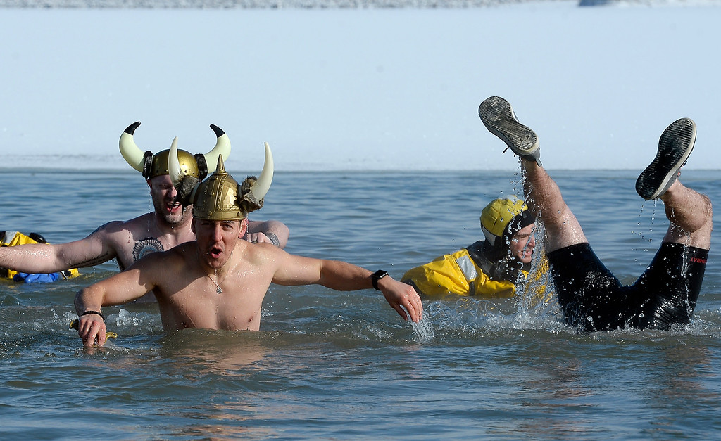 ". BOULDER, CO - January 1, 2019:  Garrett Jimenez,  front, and Dave Marucheau,  and their Viking team have conquered the water The Viking team of ""Hung Like a Norse,\"" makes the most of their time in the water  during  the annual Polar Plunge at the Boulder Reservoir on January 1, 2019. For a video and photos, go to dailycamera.com.  (Photo by Cliff Grassmick/Staff Photographer)"