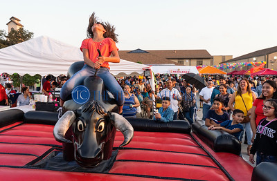 Itzel Rocha, 11, rides a mechanical bull during the annual festival at San Juan Diego Catholic Church in Dallas on Sept. 1, 2029. (David Woo Photo)