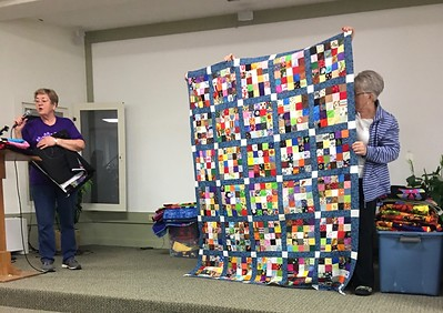 "Jan Asmann presented a quilt made from the ""Bingo Blocks"".  The bocks were made by members participating in the bingo-style game played at National Quilt Day.  Jan said the blocks were easy to work with as all were the same size and no adjustments necessary."