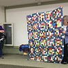 """Jan Asmann presented a quilt made from the """"Bingo Blocks"""".  The bocks were made by members participating in the bingo-style game played at National Quilt Day.  Jan said the blocks were easy to work with as all were the same size and no adjustments necessary."""