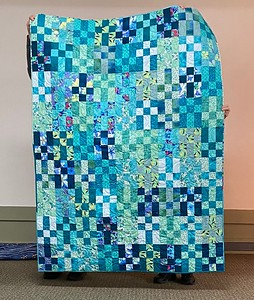 Teal Me A Story, Nina is a quilt pieced and finished by John Putnam.  Pattern by Gudrun Erla