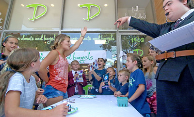 Michelle Beer, from Spring Lake, wins the older kid portion of the contest, with Tyler Cicardo as Mrs Trunchbull [on right]. The Spring Lake sidewalk sale and doughnut eating contest in Spring Lake, NJ on 8/17/19. [DANIELLA HEMINGHAUS]