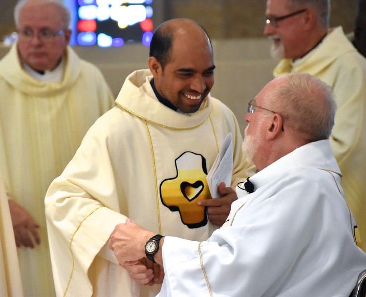 Fr. Praveen greets Fr. Ed during the Sign of Peace