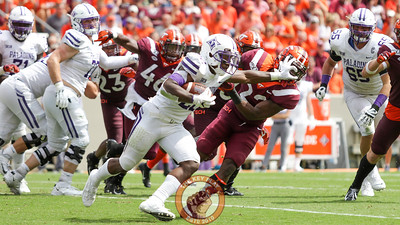 Furman running back  Devin Abrams stiffarms VT nickelback Chamarri Conner on a run. (Mark Umansky/TheKeyPlay.com)
