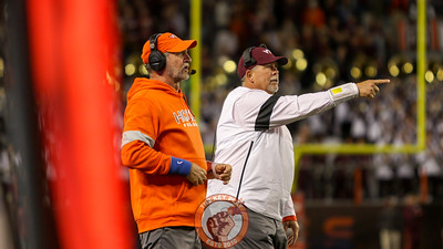 Defensive coordinator Bud Foster (orange) and defensive line coach Charley Wiles signal to their players during an overtime period. (Mark Umansky/TheKeyPlay.com)