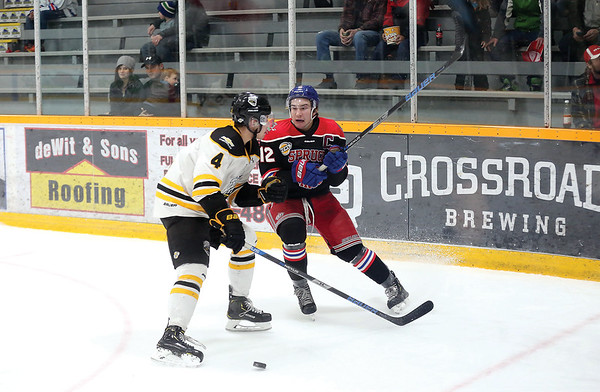 Prince George Spruce Kings forward Ben Poisson braces for impact from a check from Coquitlam Express defender Drew Cooper on Friday night at Rolling Mix Concrete Arena. Citizen Photo by James Doyle       January 25, 2019